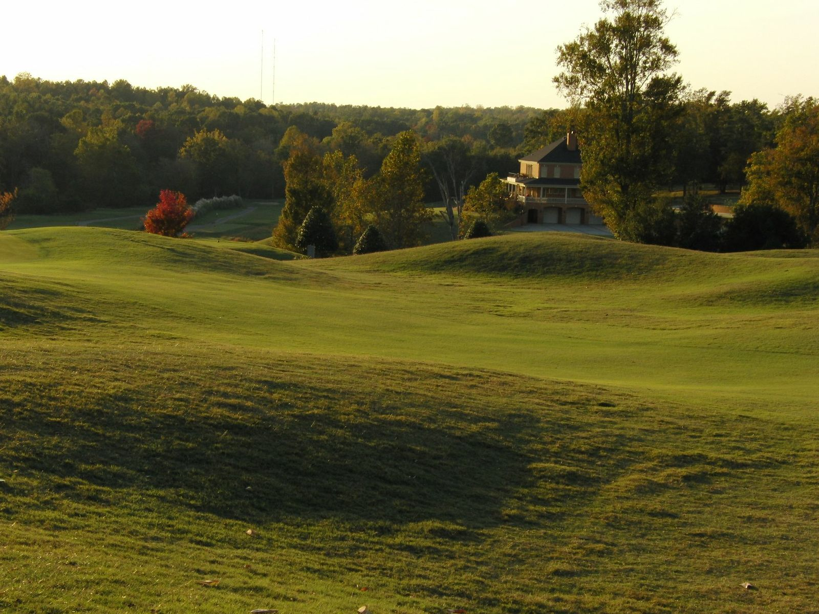 a rolling golf course with a view of the clubhouse