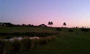 a view of the golf course and clubhouse at twilight