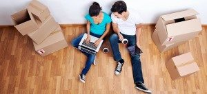 couple sitting on the floor surrounded by moving boxes using the computer