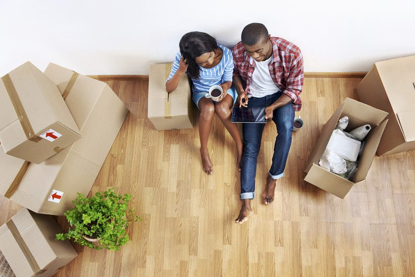 a couple sits on the floor looking at a tablet surrounded by moving boxes