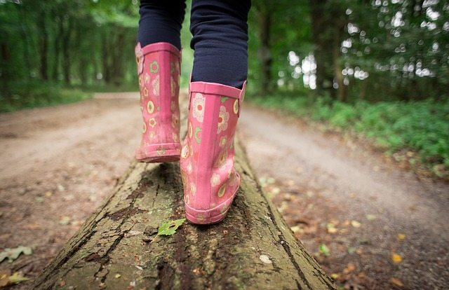 girl with pink boots walking on a log on a trail