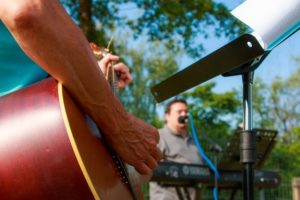 outdoor concert with man playing acoustic guitar and a man playing a keyboard