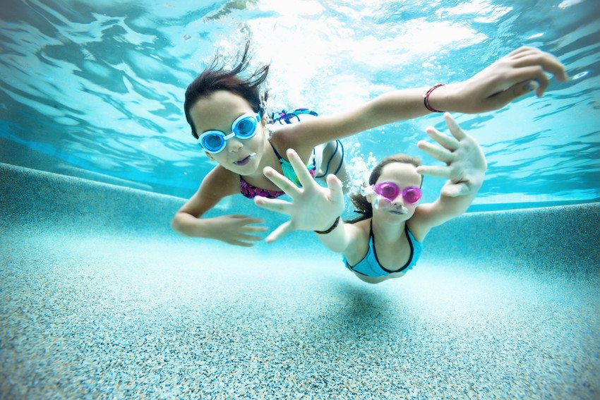 two girls wearing goggles swimming underwater towards the camera