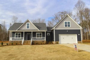 the exterior of a dark blue new construction home with front porch and attached garage.