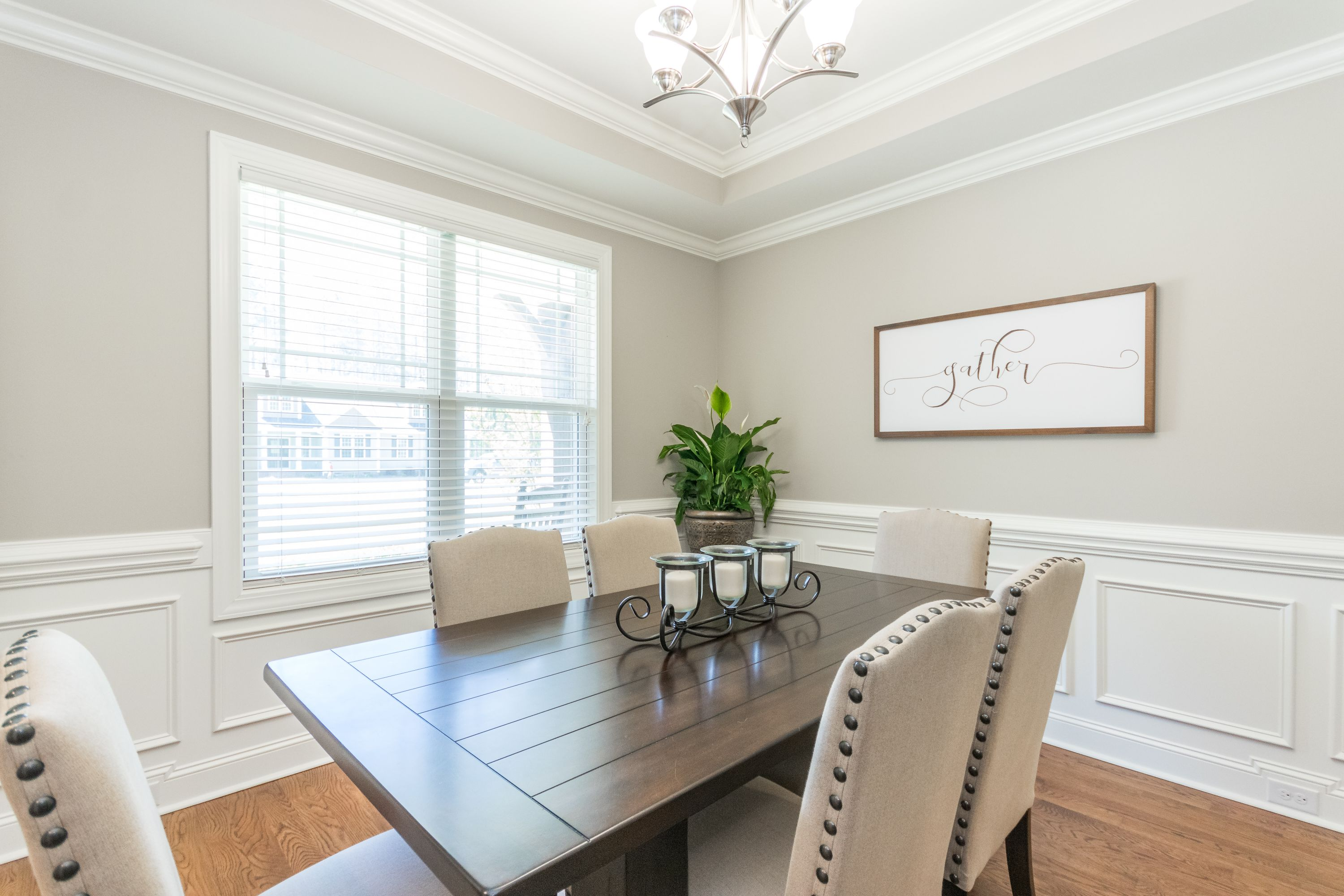 Formal dining room featuring hardwoods, wainscoting, custom trey ceiling and large gather framed artwork