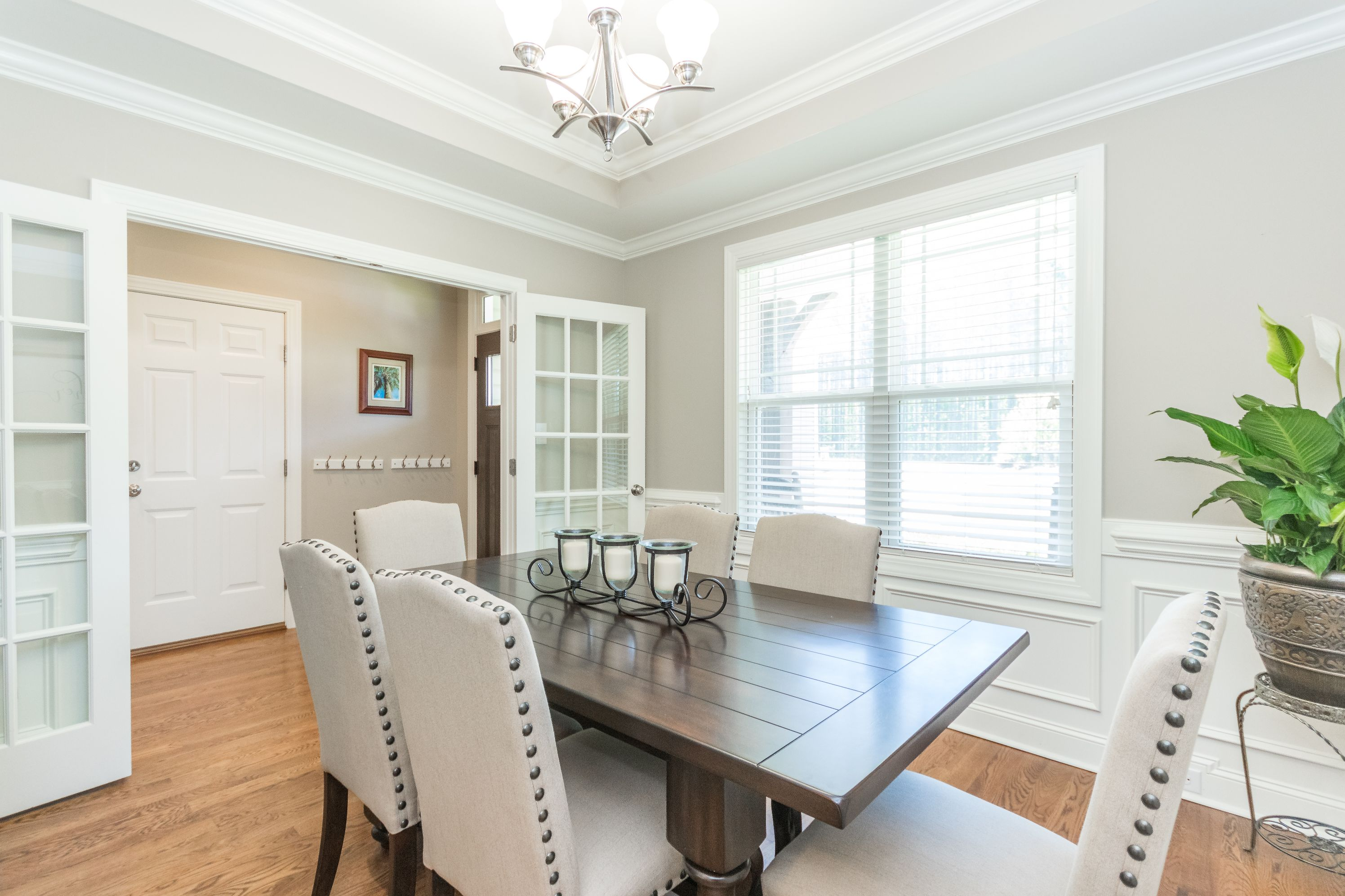 Formal dining room boasting french doors, hardwoods, wainscoting and custom trey ceiling