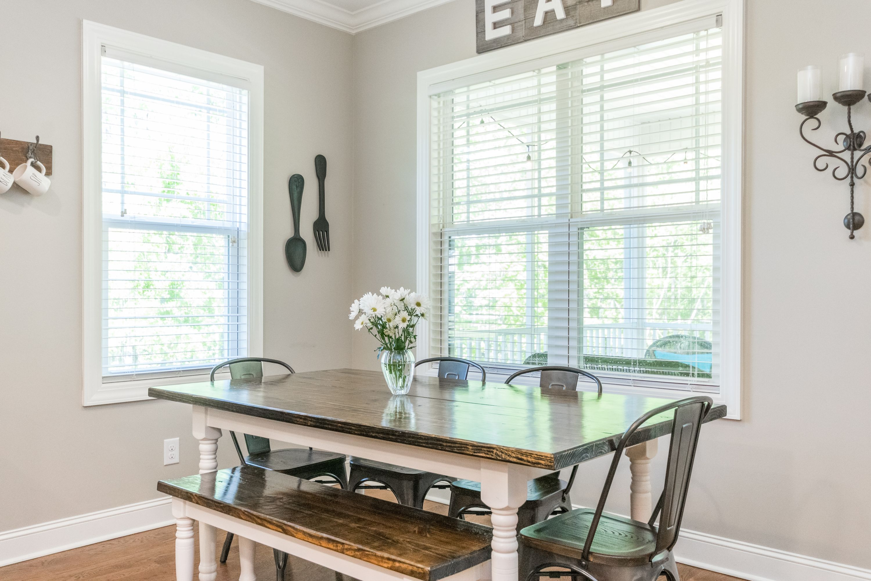 Farmhouse table with bench and metal chairs in breakfast nook is perfect for any home