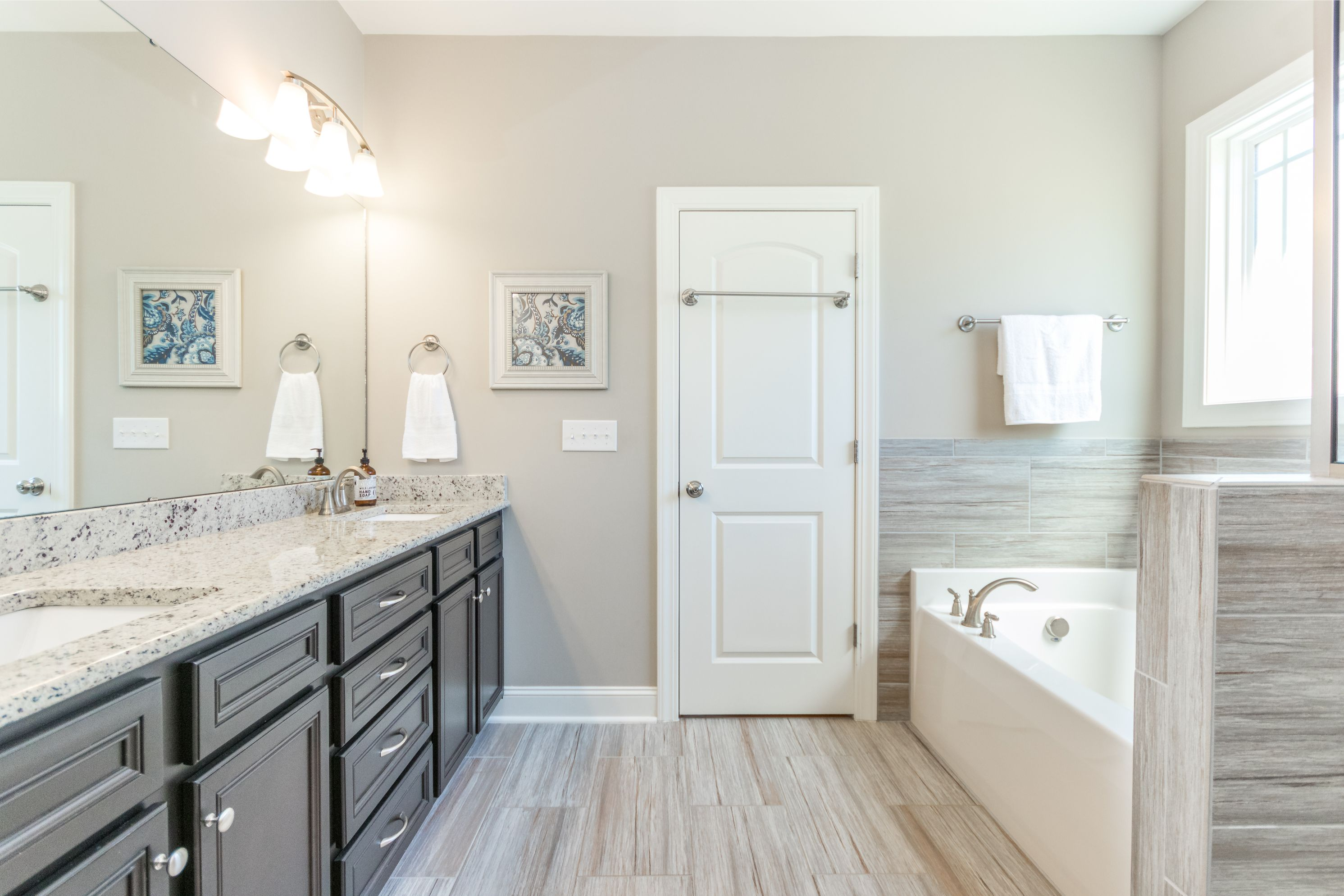 Granite bathroom countertop, gray neutral tub backsplash and flooring