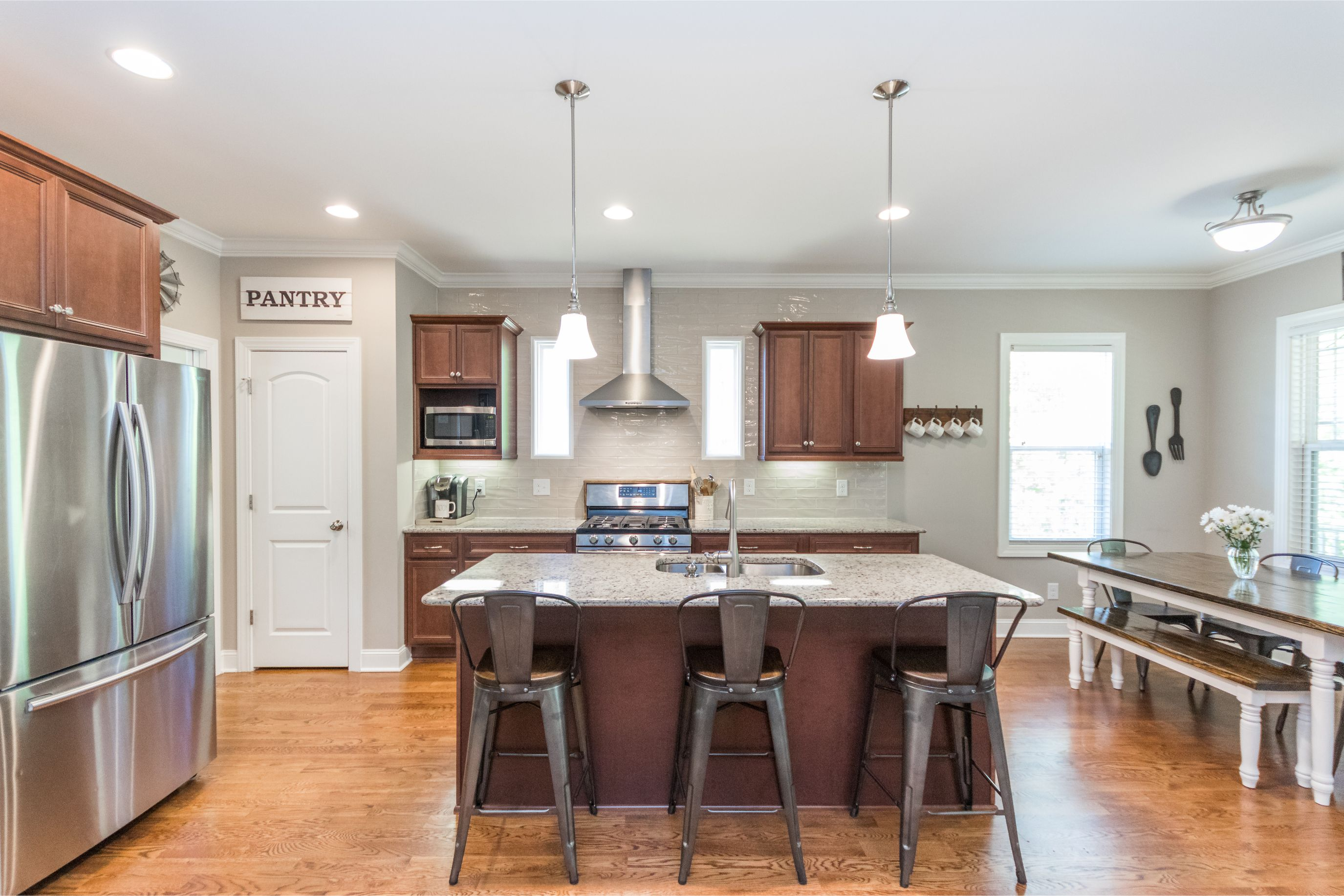 Stainless Steel appliances, white subway backsplash, metal stools, and pantry sign all bring this kitchen together